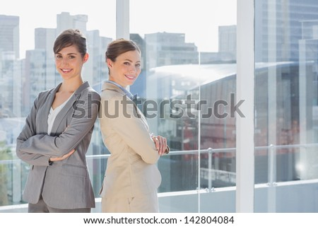 Businesswomen standing back to back in bright office