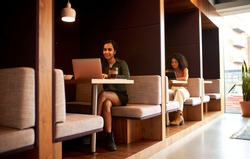 Businesswomen Working In Socially Distanced Cubicles In Modern Office During Health Pandemic