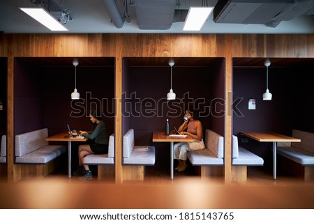 Businesswomen Working In Socially Distanced Cubicles In Modern Office During Health Pandemic ストックフォト ©