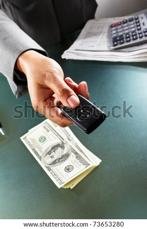busineswoman handing over car alarm device with stack of dollar bills on the table