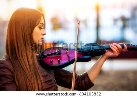 Shutterstock Busker woman perform music on violin in park outdoor. Sad beautiful girl performing jazz on city street . Spring outside with background.