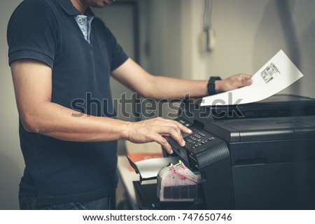 Bussiness man  hand press button on panel of printer