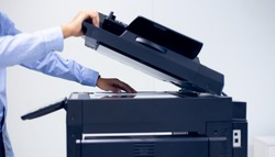 Bussiness man Hand press button on panel of printer, printer scanner laser in office copy machine supplies start concept.