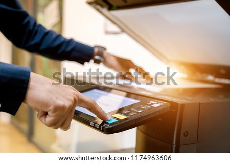 Photo of  Bussiness man Hand press button on panel of printer, printer scanner laser office copy machine supplies start concept.