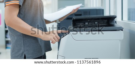 Bussiness woman Hand press button on panel of printer scanner or laser copy machine in office