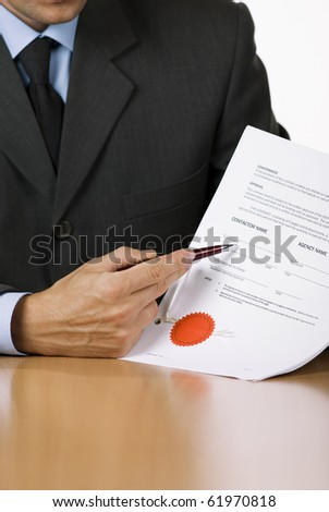 Bussinessman (or notary public) holding pen pointing at signature place on a contract document