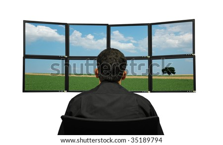 bussinessman sitting in front of group of monitors