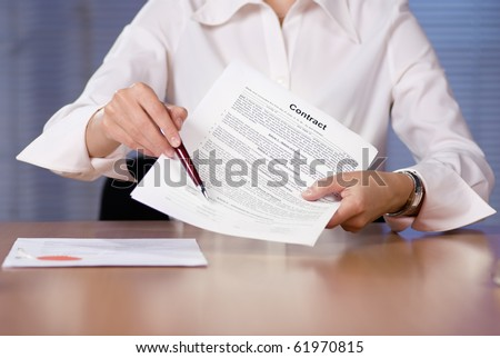 Bussinesswoman (or notary public) holding pen pointing at signature place on a contract document - stock photo