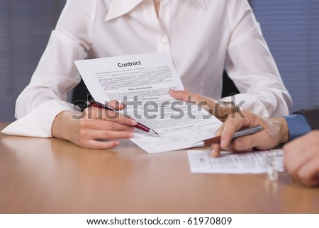 Bussinesswoman (or notary public) holding pen pointing to bussinessman at signature place on a contract document