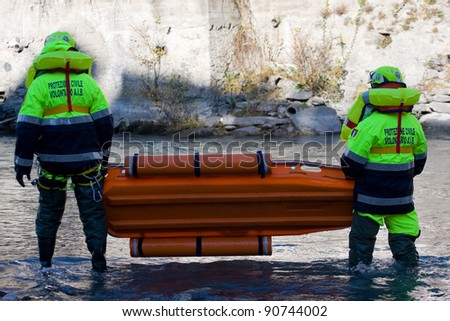 BUSSOLENO, ITALY- DECEMBER 9: Civil defense during rescue mission on December, 9, 2011 in Bussoleno, Italy. Rescue workers try to save a person fallen into the river and move with a stretcher