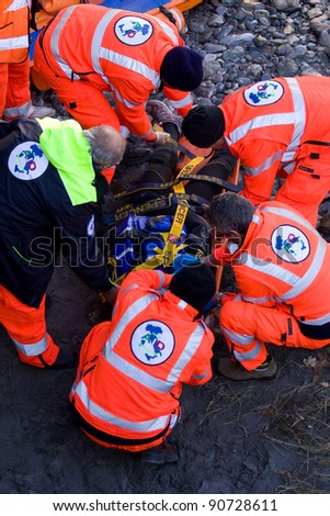 BUSSOLENO, ITALY- DECEMBER 9: Red Cross during rescue mission on December, 9, 2011 in Bussoleno, Italy. The rescue workers  move hurt person with a stretcher