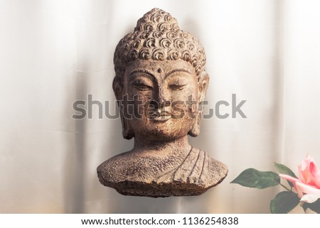 Bust of the Buddha with a cracked paint finish floating in front of a silk background. Some leaves and a rose can be partially seen in the bottom right corner.