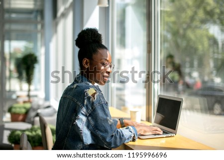 Busy African American woman in denim jacket working on digital tablet at sunny cafe interrior at the big window, back view. Pensive woman surfing internet pages during her breakfast.