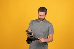 busy bearded man videographer making movie for vlogging with camcorder, cameraman