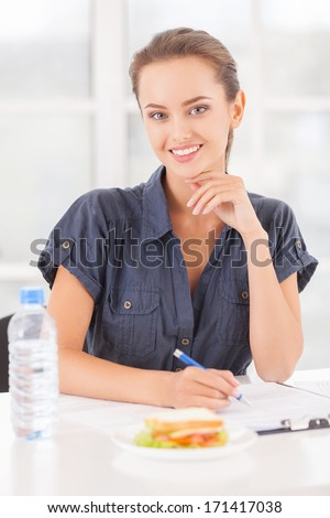 Busy beauty. Beautiful young woman writing something in her note pad and smiling while sandwich and a bottle of water laying on the table