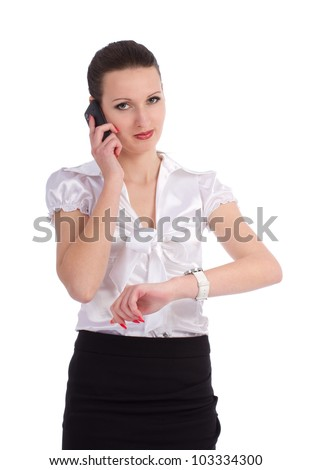 Busy business woman checking time while talking on cellphone over white background