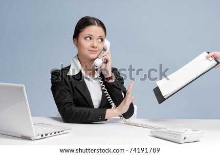 Busy business woman in office talking by phone and sign a papers at work place.  Not now!