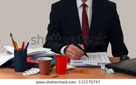 Busy businessman or office worker, at untidy desk