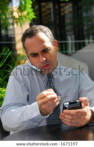 Busy businessman talking on cell phone and working on his palm pilot