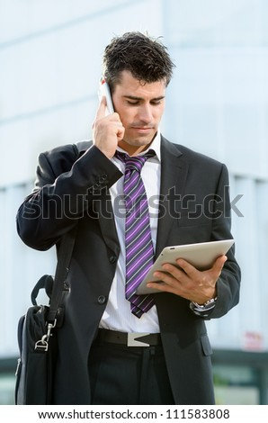 Busy businessman with cell phone. Man looking tablet making business call outdoor. Handsome caucasian male model.