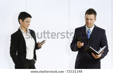 Busy businesspeople using mobile phone and personal organizer.?