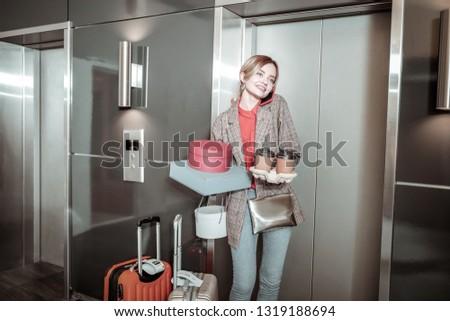 Busy businesswoman. Busy businesswoman standing near luggage calling her boyfriend waiting for him near elevator #1319188694