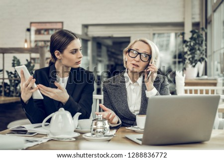 Busy businesswoman. Busy businesswoman wearing white blouse and grey jacket speaking by phone #1288836772