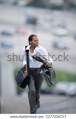 Busy businesswoman running outdoors late for city meeting