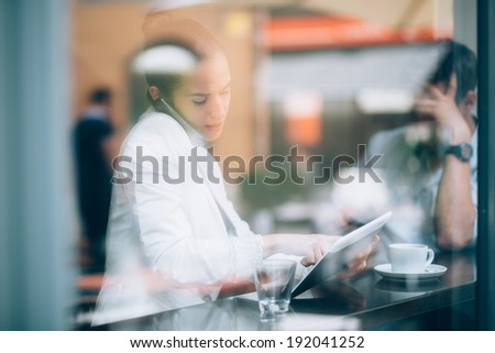 Busy businesswoman talking on phone and using tablet computer in coffee shop stock photo
