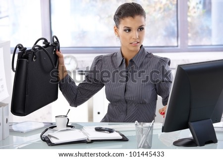 Busy businesswoman working at desk in bright office.