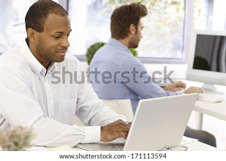 Busy casual office workers sitting at desk, working with computer. - stock photo