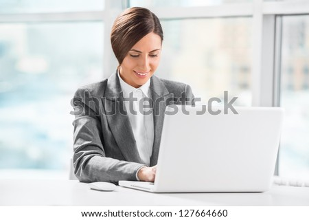 Busy caucasian business woman using laptop at office desk - stock photo