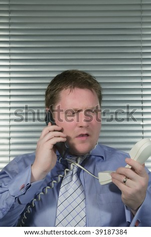 Busy Caucasian Businessman getting stressed using two telephones,