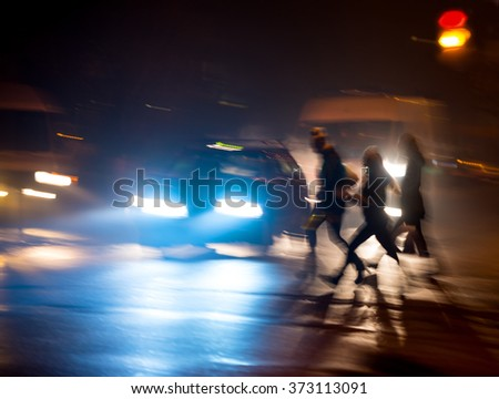 Busy city street people on zebra crossing at night. Dangerous situation. Intentional motion blur #373113091