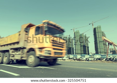 Busy construction site, a large truck speed by. #325504751