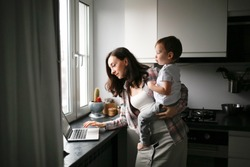 Busy cute woman mom with a baby in her arms works on a laptop in the kitchen. Family concept and freelance work, Authentic life style and toning.