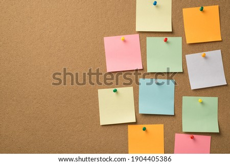 Busy day at work concept. Photo of lot of colorful notepaper attached with pins to the wooden board Stock photo ©