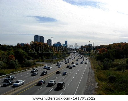 busy day time rush hour traffic. six lane Don Valley Parkway Highway in Toronto. diminishing perspective with multi level residential condominium buildings along the highway. blue sky and white clouds stock photo