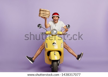 Busy deliveryman being in hurry, carries cardboard boxes with pizza, delivers to customers, poses on yellow scooter, wears helmet, white t shirt and sportshoes, spreads legs, has happy expression