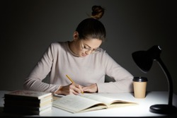Busy freelancer rewrites infrormation into notepad, prepares article for publication, reads books, writes some notes in organizer, drinks takeaway coffee, sits in darkness, wears round big spectacles