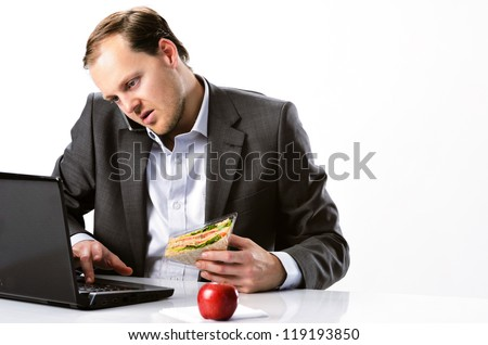 Busy hardworking businessman multitasking, talking on mobile cell phone typing on laptop computer and having healthy sandwich lunch with red apple