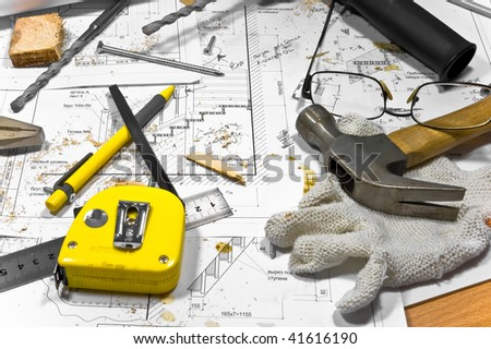 Busy hobby workbench. Different carpenter tools: hummer, tape measure, ruller, drill, pliers and a pencil are lying upon the blueprints and drawings along with screws, gloves and grasses.