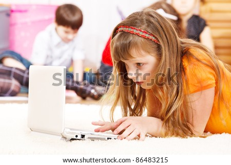 Busy kid lie watching laptop screen