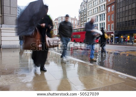 Busy london commuters in the pouring rain with umbrellas and coats