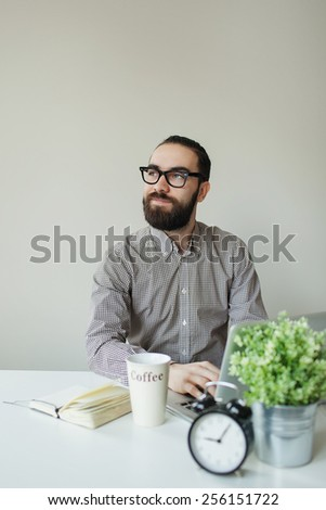 Busy man with beard in glasses thinking over laptop with coffee on the table