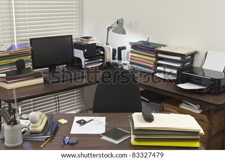 Busy, messy corner office with piles of files.