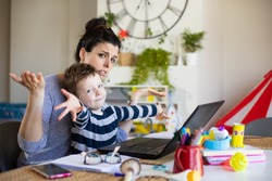 Busy mother working from home and taking care of her child. Stressed woman telecommuting on laptop computer with her son.