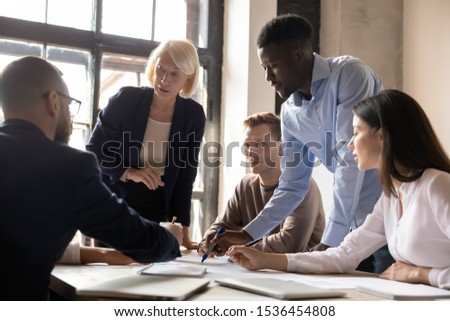 Busy multiethnic old and young businesspeople group working together planning corporate startup project in teamwork analyze financial report discussing marketing result at team office briefing table