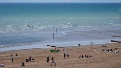 Busy pebble beach southern England. English seaside busy weekend. Public on beach sunny day seaside town