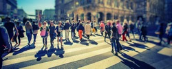 Busy Pedestrian Crossing over zebra on sunny day in the city